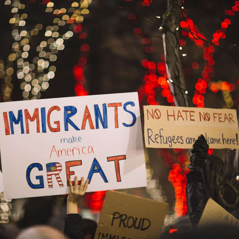 Protesters holding signs reading Immigrants make America Great