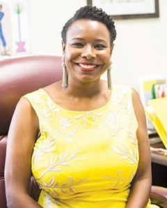 Oklahoma City Ward 7 Councilwoman Nikki Nice depicted in yellow dress sitting at her desk.