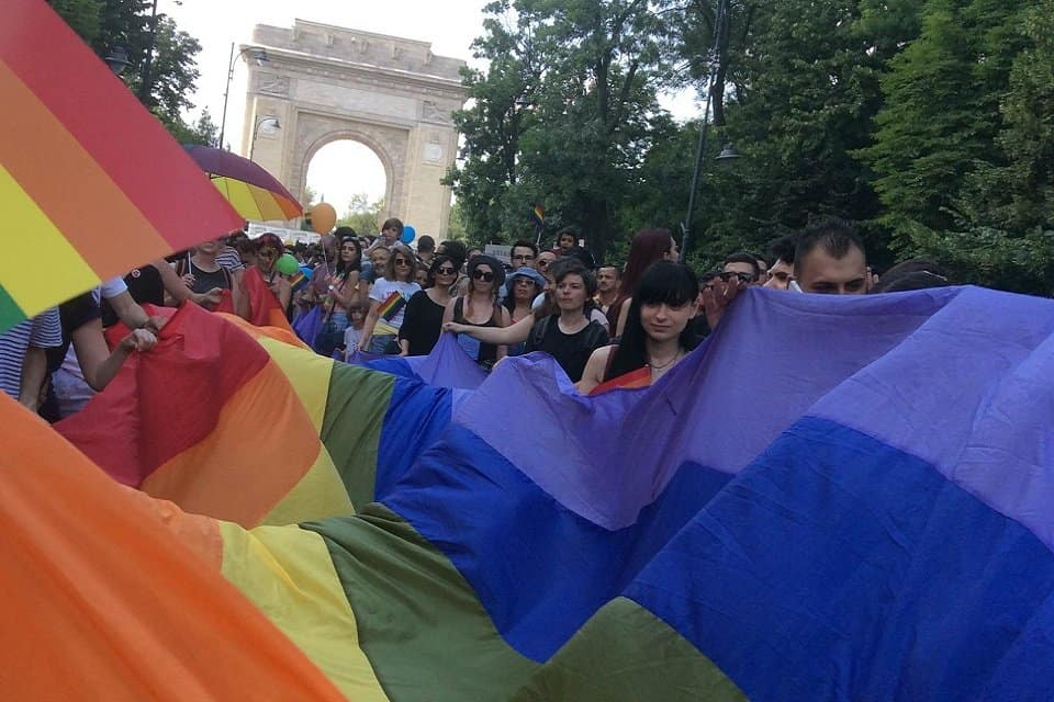 People holding a long rainbow flag in front of the Romanian Triumph Arch in Bucharest, during Pride.
