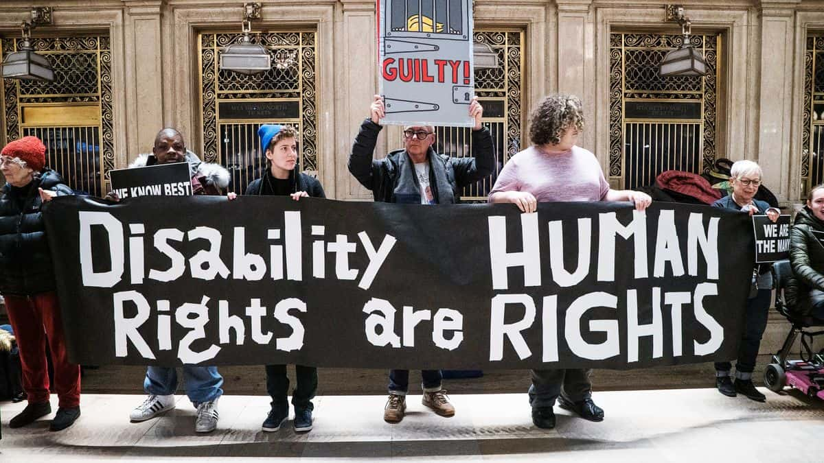 Picture of protesters holding sign reading disability rights are human rights
